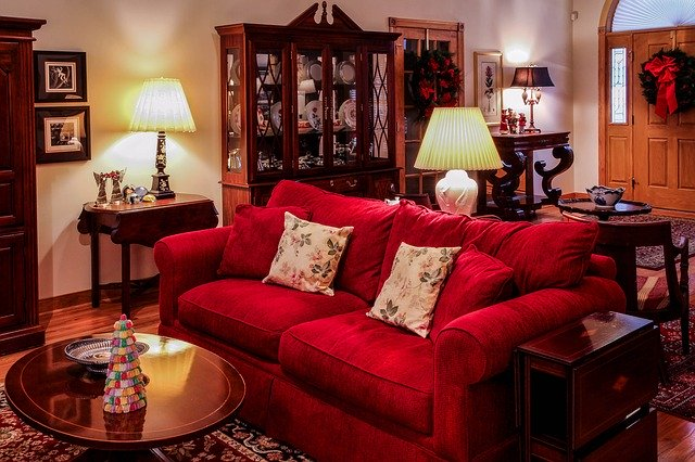 living room decorated with red sofa, lamp and table