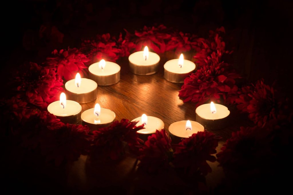 Heart shaped rose petals and candles in bedroom romantic decor