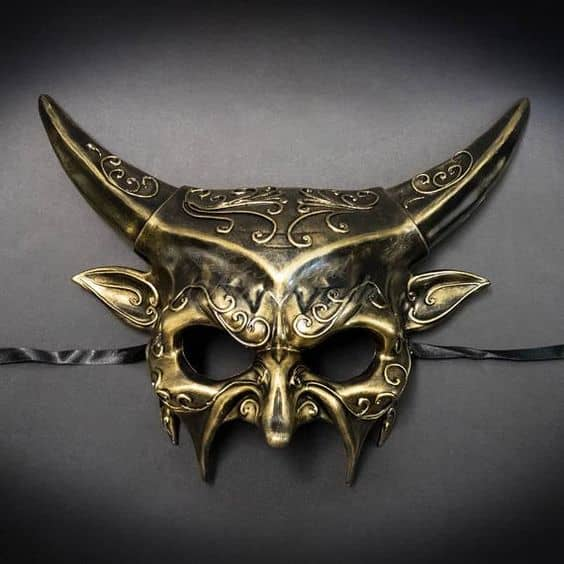 golden mask hanging on a grey wall