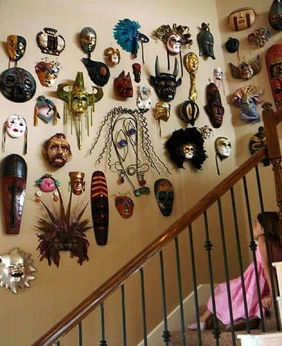 masks hanging on staircase wall
