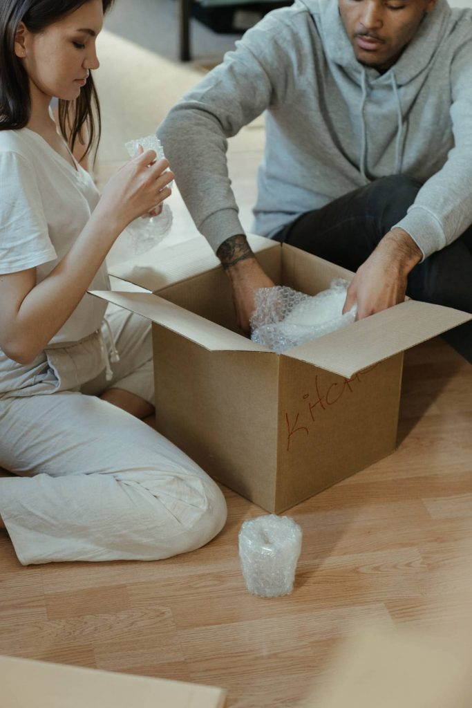 man and woman packing glassware in a moving box